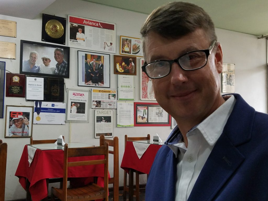 Tom in the dining room with pictures and honorable mentions of Chez Wong in Lima, Peru