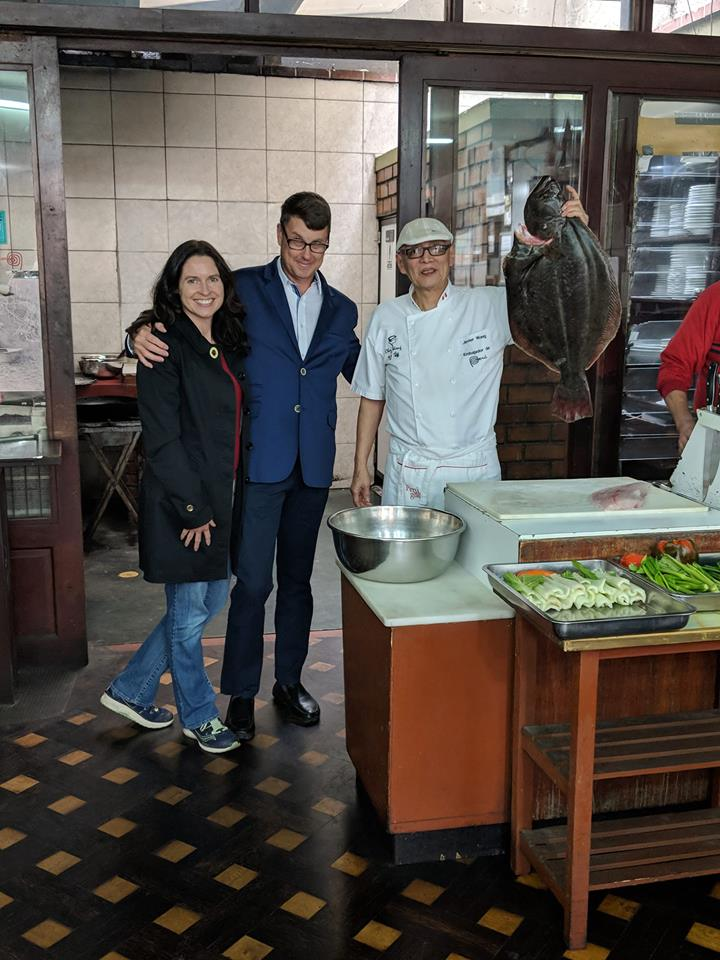 Tiffany and Tom posing with Cheaz Wong holding a turbot at his restaurant in Lima, Peru
